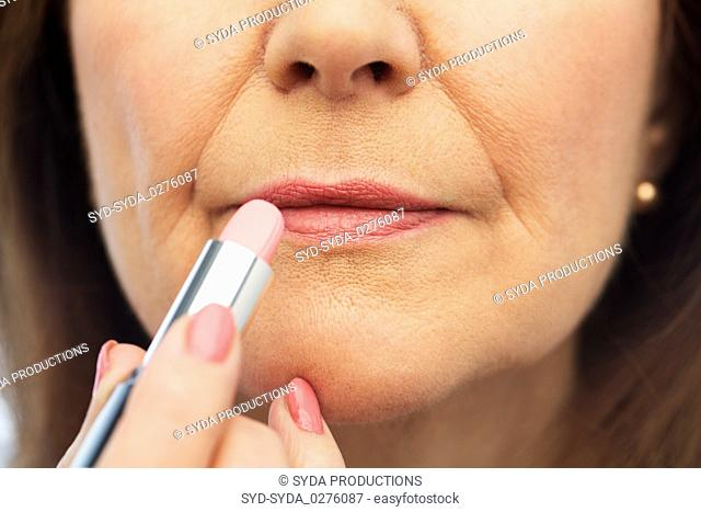 close up of senior woman applying lipstick