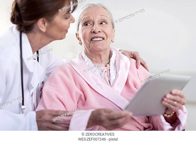 Doctor and smiling elderly patient in wheelchair with digital tablet