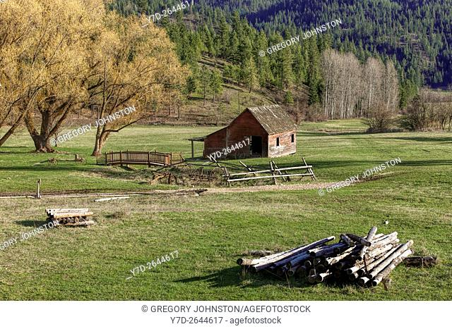 An old barn sits in a quaint little meadow next to some trees in north Idaho