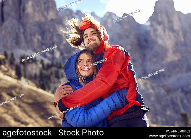 Happy young couple hugging in windy mountains