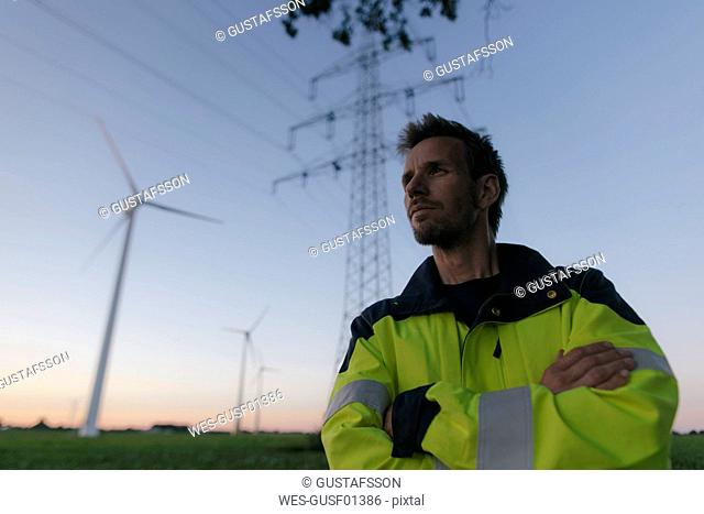 Portrait of an engineer next to a wind farm and power pole