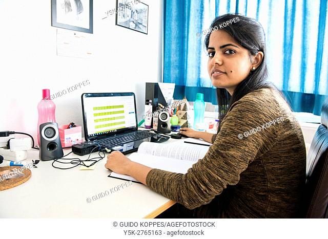 Aachen, Germany. Young, Indian university exchange student working inside her dormatory room on assignments and study