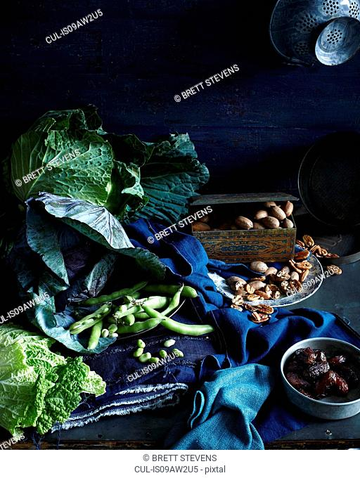 Still life with seasonal cabbage, green beans, dates and pecans