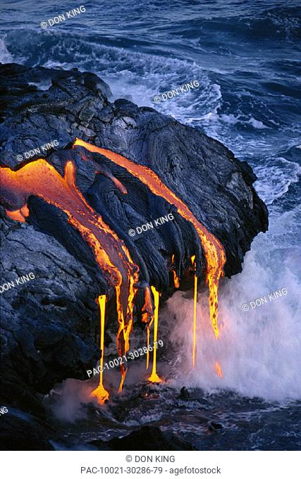 Hawaii Volcano National Park closeup lava flowing into gray ocean, steam smoke pahoehoe