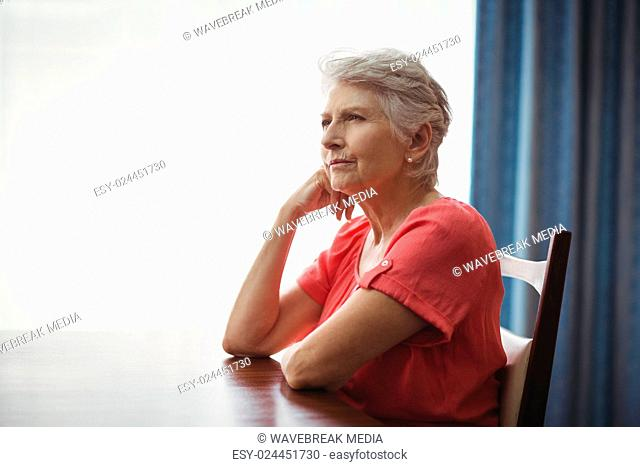 Thoughtful senior woman sitting at a table