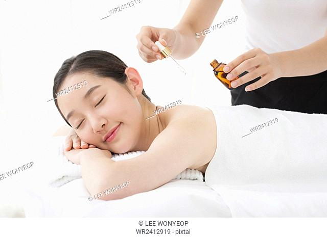 Side view portrait of young smiling woman getting essential oil on her skin closing her eyes