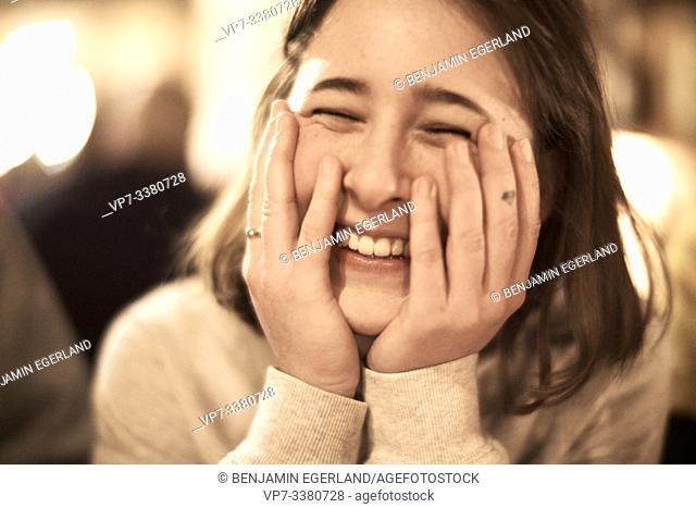 headshot of happy woman indoors in restaurant
