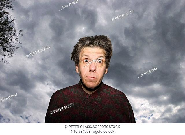 Middle-age man posing in front of a cloudy sky