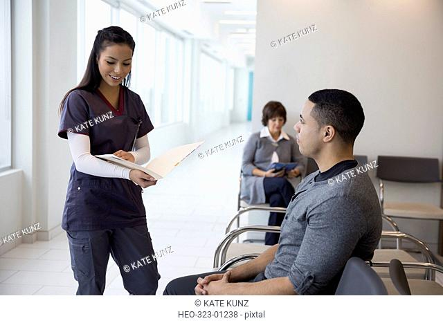 Female nurse with medical chart talking to male patient in waiting room