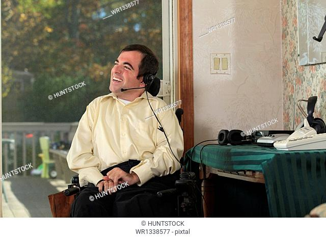 Man with Cerebral Palsy in motorized wheelchair using his earphones