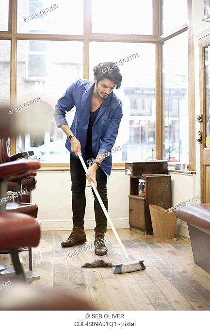Man sweeping barbershop floor with broom
