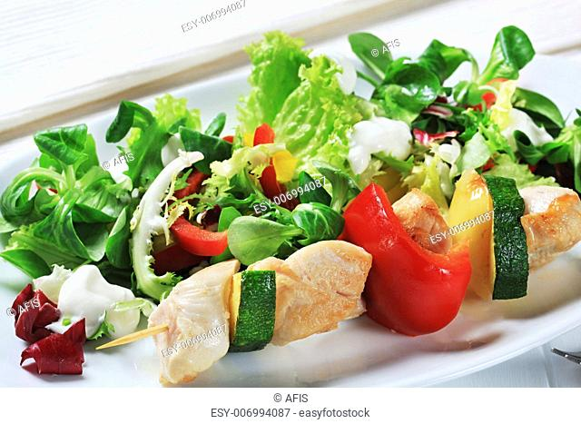 Chicken skewer with mixed salad greens