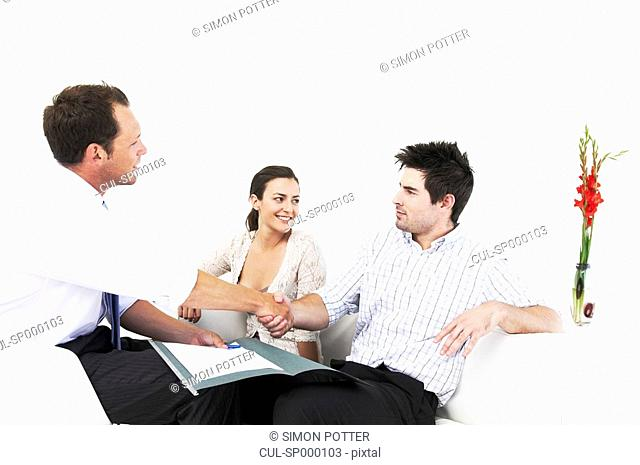 Salesman shakes hands with couple