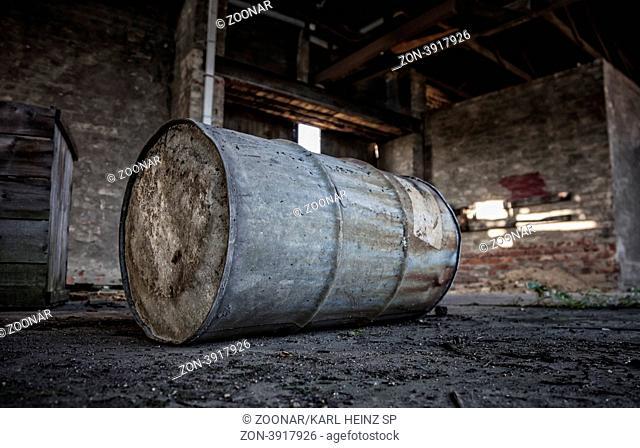 alte Metalltonne lagert in einer maroden Halle