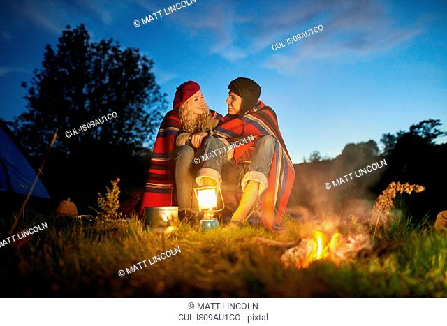 Young camping couple sitting by campfire at dusk