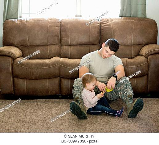 Male soldier playing with daughter in living room at air force military base