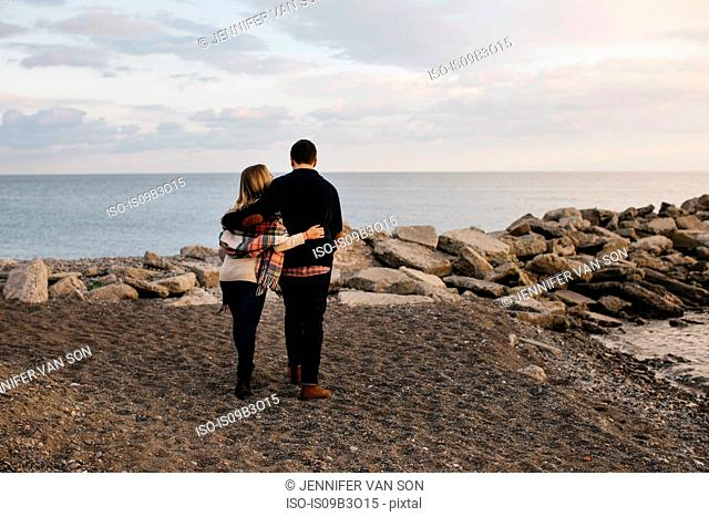 Young couple standing beside sea, rear view