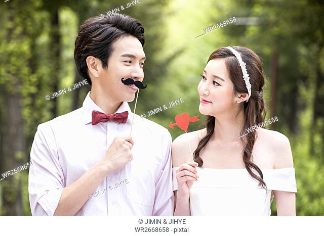 Portrait of young smiling wedding couple posing face to face outdoors