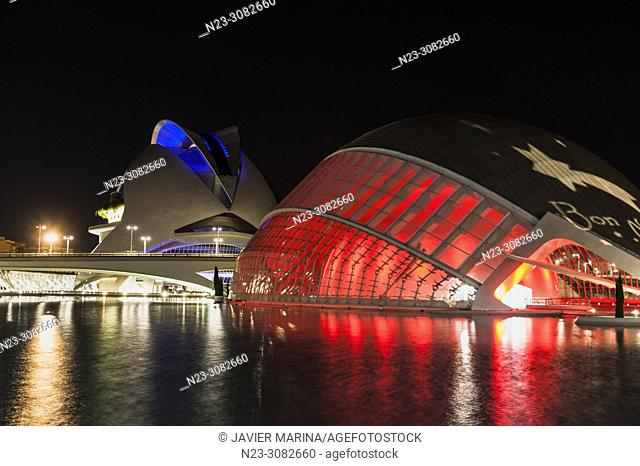 Palace of Arts and Hemisferic illuminated in the city of arts and sciences, behind the building Torre de Francia, Valencia, Spain