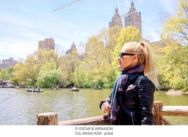 Female tourist looking out at boating lake in Central Park, New York, USA