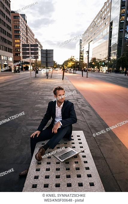 Germany, Berlin, Potsdamer Platz, businessman sitting on bench with laptop in the evening