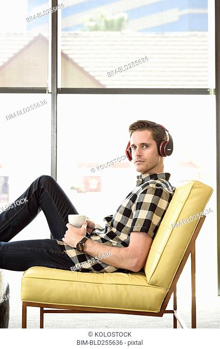 Caucasian man drinking coffee and listening to headphones
