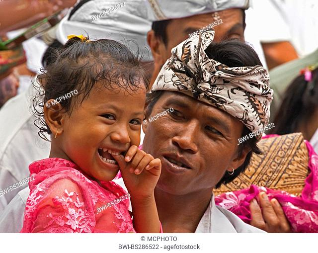 A BALINESE father and daughter at PURA BEJI in the village of Mas during the GALUNGAN FESTIVAL , Indonesia, Bali, Ubud