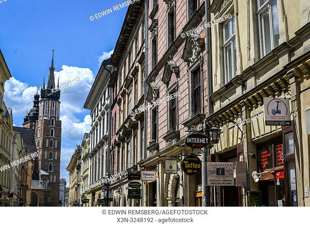 Exteriors of historic townhouses being used as shops in Main Market Square in Krak—w Old Town with Church of Our Lady Assumed into Heaven (St