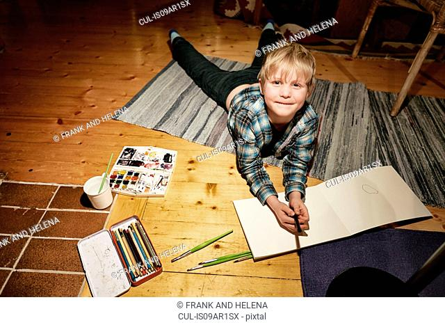 Boy lying on floor with watercolor paints and sketch pad