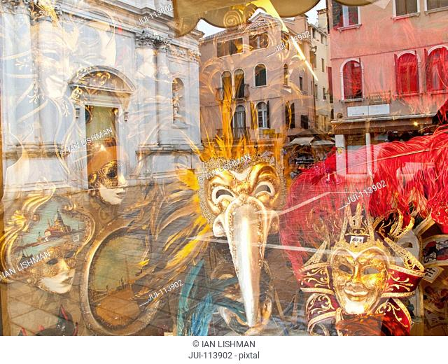 Ornate Venetian masks for Venice Carnival on display in shop window with architectural reflection, Italy