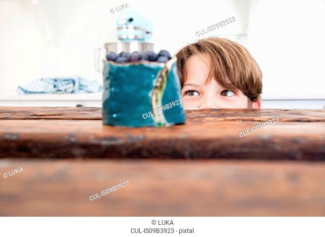 Young boy peering over kitchen work surface, looking at bowl of blueberries