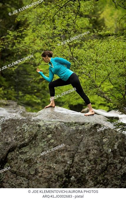 Woman practicing yoga in lunge pose on boulder in forest, Gorham, New Hampshire, USA