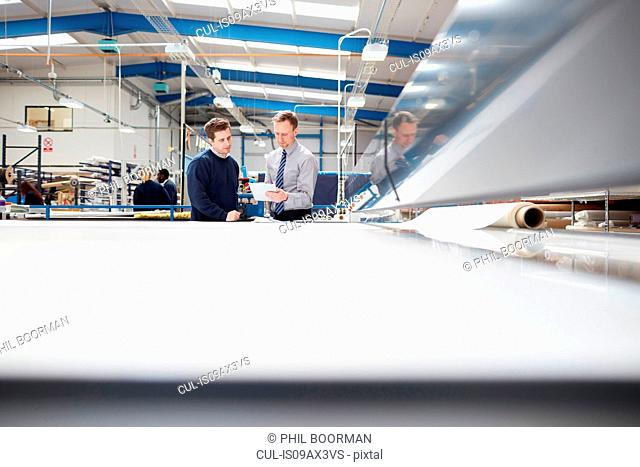 Manager and factory worker discussing work in roller blind factory