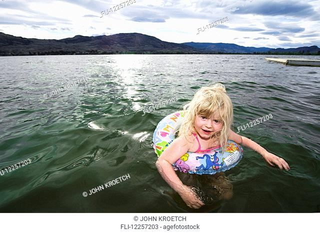 Young blonde girl floating in a lifebuoy; Osoyoos, British Columbia, Canada