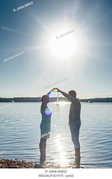 Couple standing at Lake Cospuden, forming heart with hands against the sun