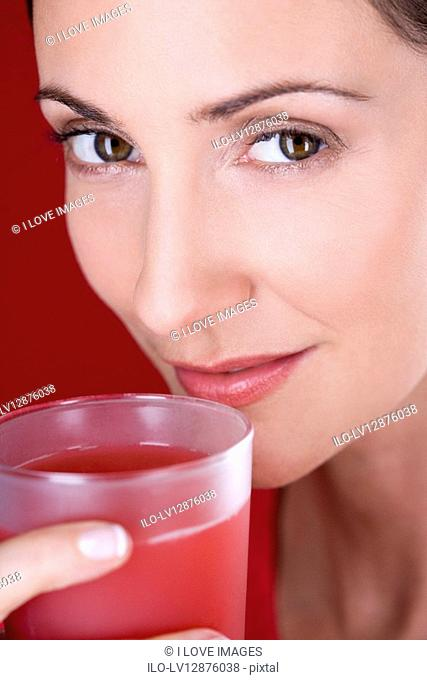 A mid adult woman drinking a glass of fruit juice