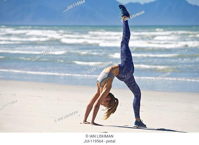 Woman Wearing Sportswear In Gymnastic Pose On Beach In South Africa