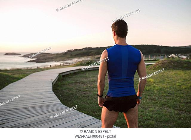 Spain, Ferrol, back view of a jogger standing on boardwalk