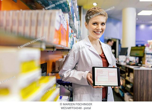 Portrait of smiling pharmacist in pharmacy holding tablet with digital prescription