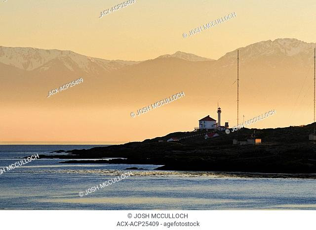 The Olympic Mountains provide a dramatic backdrop for Trial Island Light near Victoria BC
