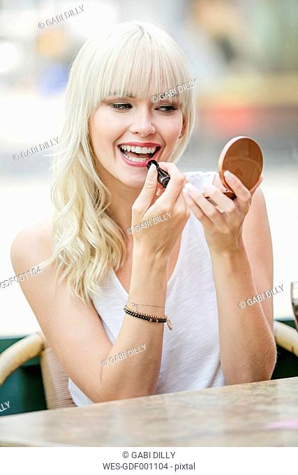 Portrait of blond woman sitting at sidewalk cafe applying lipstick