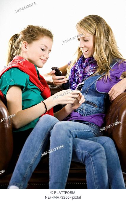 Teenage girls using a mobile phone