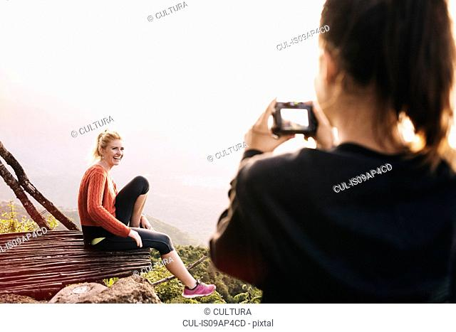 Over shoulder view of young woman photographing friend at Lake Atitlan, Guatemala