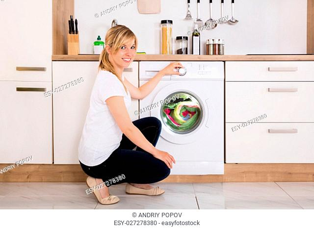 Young Woman Cleaning Multi-colored Clothes In Washing Machine At Home