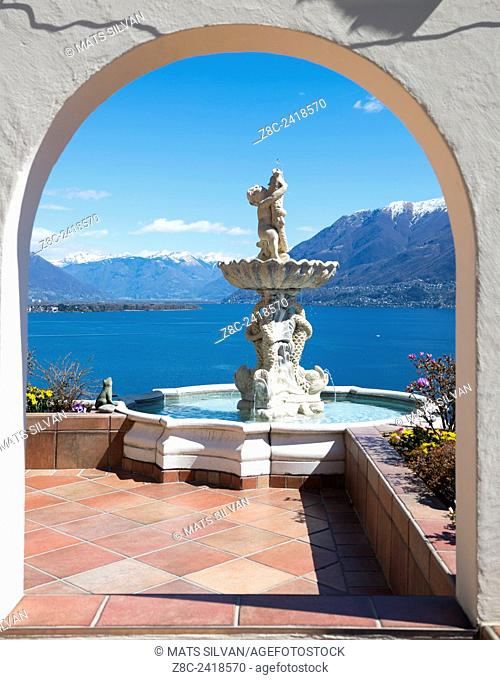 Window view with a water fountain with statue and panoramic view over alpine lake Maggiore with snow-capped mountains in a sunny day with blue sky in Ticino
