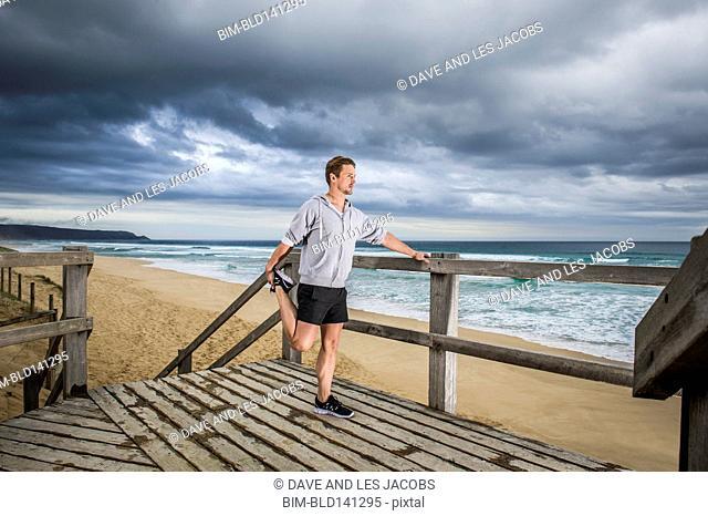 Caucasian runner stretching on wooden boardwalk at beach