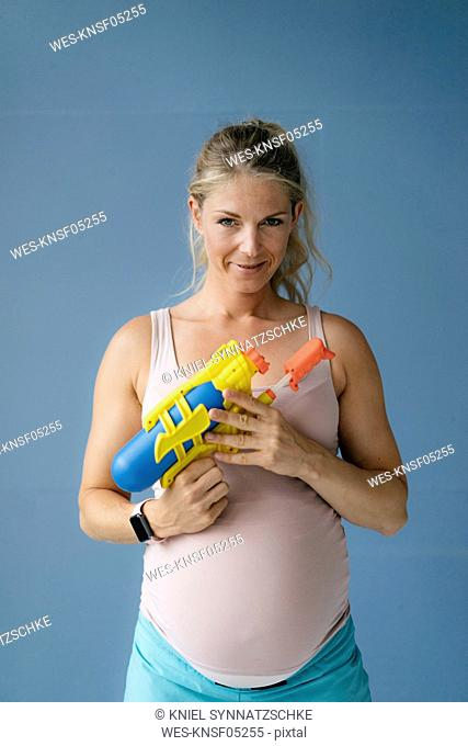 Portrait of smiling pregnant woman holding water gun