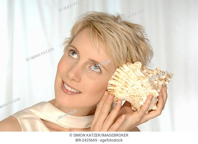 Young woman holding large shell to her ear, listening
