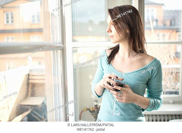 Woman standing by a window, looking away. Concept of sadness, waiting and anticipation. Lifestyle image of contemplation