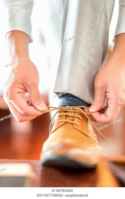 Businessman or groom tied a shoelace on his brown shoes. Selective focus